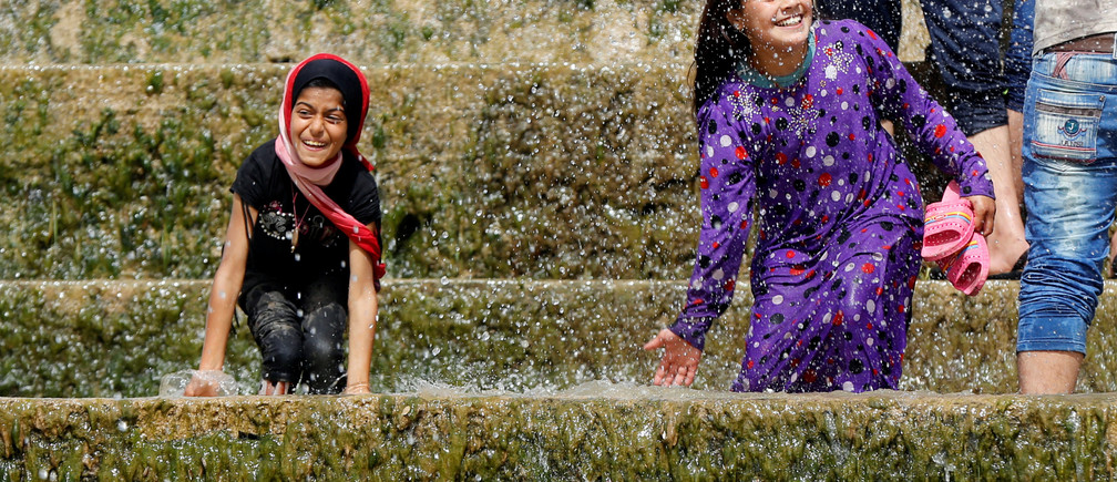 """Iraqi girls play with water as they enjoy their Friday holiday with their family at Shallalat district (Arabic for """"waterfalls"""") in eastern Mosul, Iraq, April 21, 2017. REUTERS/ Muhammad Hamed - RTS13CR3"""
