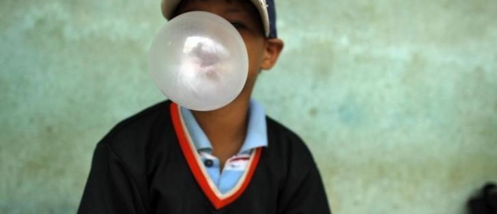 A child blows a bubble gum as he attends a donation of baseball equipments organized by Homerun hopefuls in Santo Domingo July 12, 2011. Homerun hopefuls is an American non-profit organization that collects both new and slightly used baseball equipment for impoverished children in the Dominican Republic. REUTERS/Eduardo Munoz (DOMINICAN REPUBLIC - Tags: SPORT BASEBALL SOCIETY FOOD)