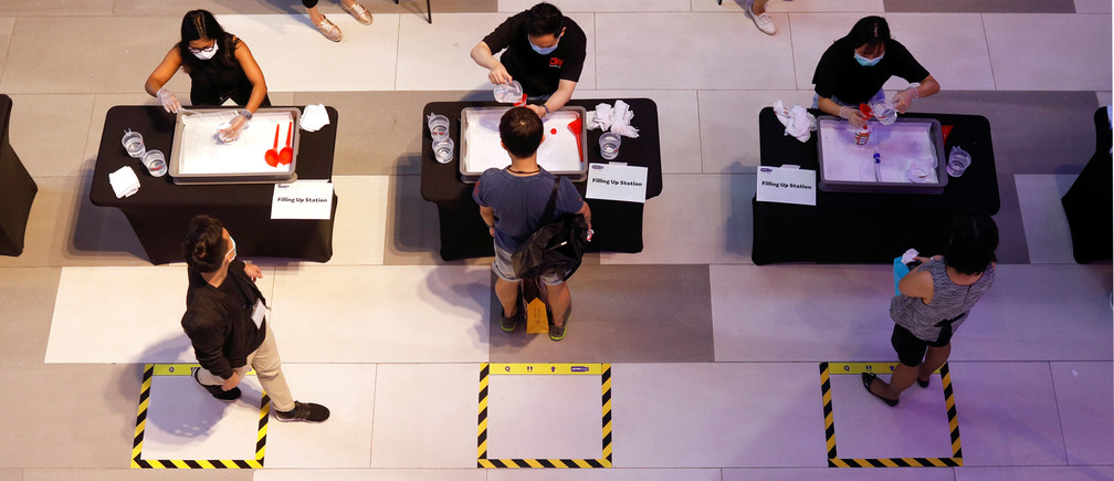 People queue to get a free refill of hand sanitiser at a mall , as the spread of coronavirus disease (COVID-19) continues, in Singapore, April 1, 2020.