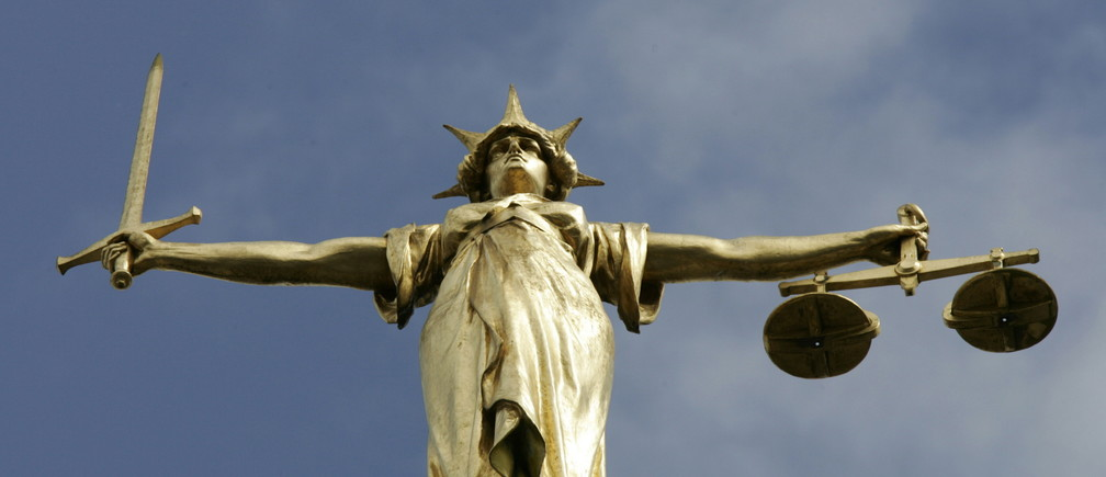 The Statue of Justice, depicted as a women with a sword in one hand and scale in her other, is seen on top of the London Central Criminal Court, the Old Bailey in London August 12, 2005. Britain may reform laws to ensure efforts to deport foreign nationals deemed a threat to national security, are not blocked by judges over human rights concerns. - PBEAHUNXWFA