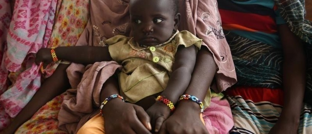 A woman holds her child as they wait to receive treatment in Kobo health center in Kobo village, one of the drought stricken areas of Oromia region, in Ethiopia