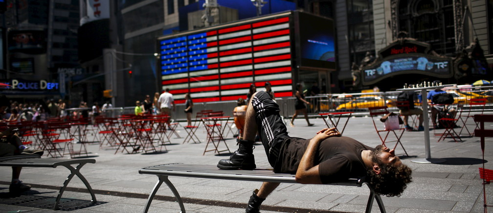 A man takes a nap during a sunny day in Times Square in New York July 19, 2015. REUTERS/Eduardo Munoz - GF10000164260