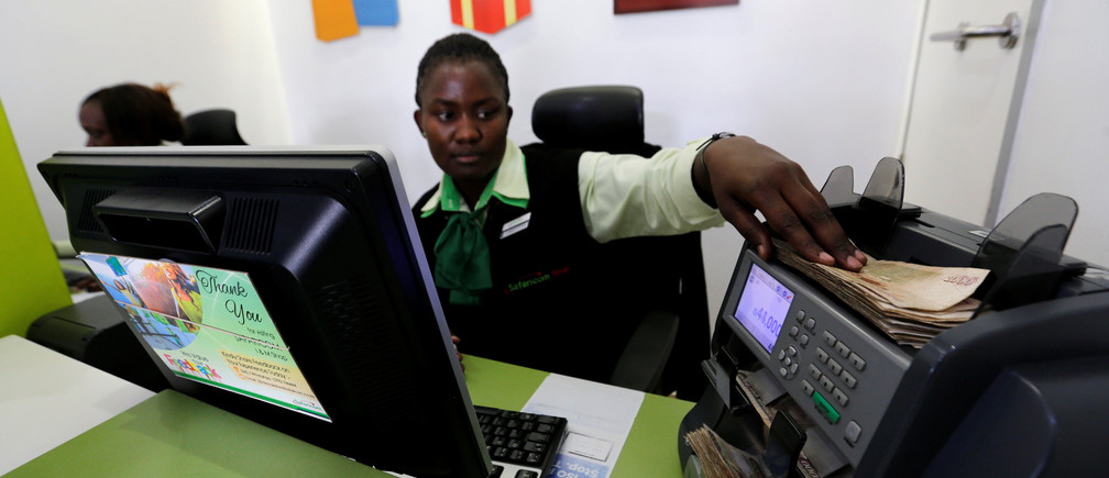 An employee uses a money-counting machine as she serves a customer inside a mobile-phone care centre in Nairobi.