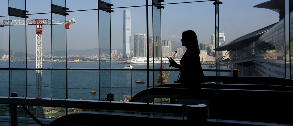 ICC, the tallest skyscraper in Hong Kong, is seen in Kowloon Peninsula, as a woman ascends on an escalator inside the Hong Kong Convention and Exhibition Centre, where the Asian Financial Forum is held in Hong Kong, China January 18, 2016.