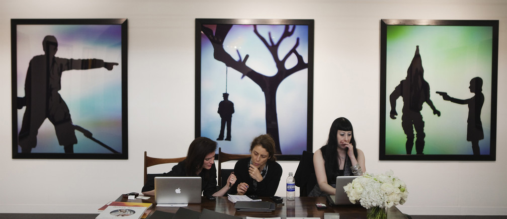 Women work at a desk while sitting in front of artwork by artist Andres Serrano during the 2012 Armory Show art fair in New York March 8, 2012. REUTERS/Lucas Jackson (UNITED STATES - Tags: SOCIETY) - GM1E8390V4K01