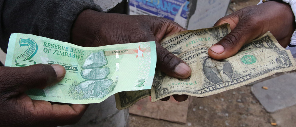 Illegal money changers pose while exchanging a new Zimbabwe bond note (L) and U.S. dollar notes in the capital Harare, Zimbabwe, November 28, 2016. REUTERS/Philimon Bulawayo - RC130F5B2970