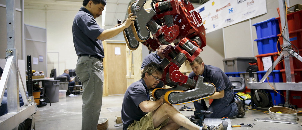 Mark Waldbaum (C) of Team Tartan Rescue CHIMP (CMU Highly Intelligent Mobile Platform) robot from Carnegie Mellon University has its tracks changed in the team garage during the finals of the Defense Advanced Research Projects Agency (DARPA) Robotic Challenge in Pomona, California June 6, 2015. Twenty-four teams are competing to win a portion of a $3.5 million prize by operating humanoid robots across a task and obstacle course.  REUTERS/Patrick T. Fallon - GF10000119295