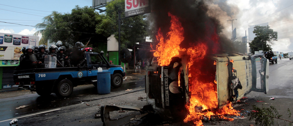 Riot police officers travel past a burning police car during a protest against Nicaraguan President Daniel Ortega's government in Managua, Nicaragua September 2, 2018.REUTERS/Oswaldo Rivas      TPX IMAGES OF THE DAY - RC1CB8A23AC0