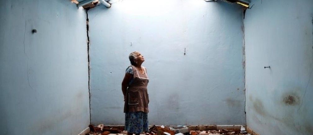 """Tomasa Mozo, 69, a housewife, looks up at the roof as she poses for a portrait inside the ruins of her house after an earthquake in San Jose Platanar, at the epicentre zone, Mexico, September 28, 2017. The house was badly damaged but with the help of her family Mozo rescued some furniture. She lives in another room of her house and hopes to repair the damage as soon as possible. """"I'm afraid to go out, I can not sleep,"""" Mozo said. REUTERS/Edgard Garrido  SEARCH """"GARRIDO PORTRAIT"""" FOR THIS STORY. SEARCH """"WIDER IMAGE"""" FOR ALL STORIES. TPX IMAGES OF THE DAY. - RC1DC662B340"""
