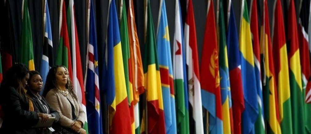 Women stand in front of some of the flags representing the 54 sovereign states that are members of the AU, at the end of the 25th African Union summit in Johannesburg, June 15, 2015.   REUTERS/Siphiwe Sibeko - RTX1GN64