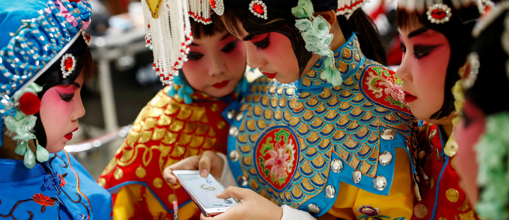 A participant plays a game on her phone as others watch during a break in a traditional Chinese opera competition at the National Academy of Chinese Theatre Arts in Beijing, China, November 26, 2016. REUTERS/Thomas Peter TPX IMAGES OF THE DAY - RC134BA8F8F0