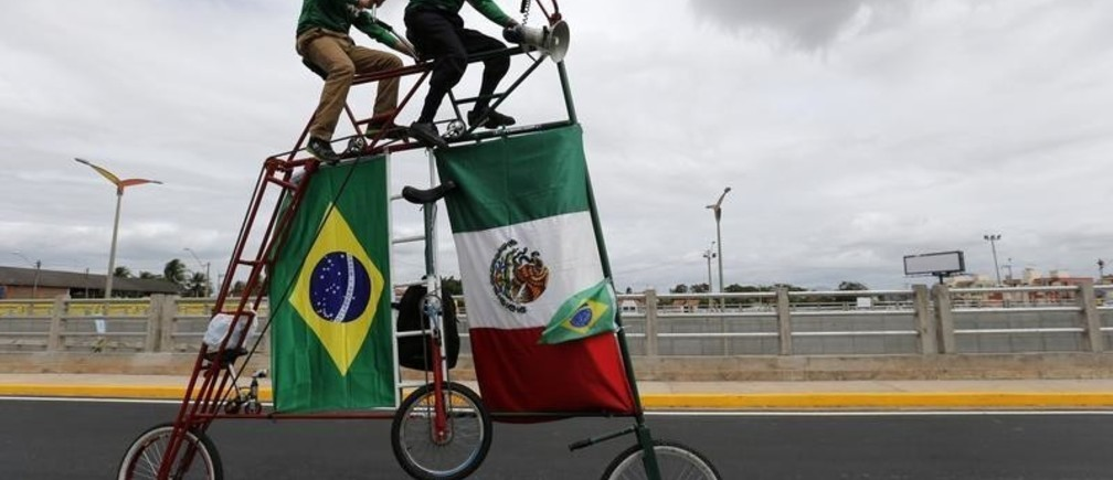 Fans of Mexico ride a big bike as they arrive at the Castelao stadium before Mexico's 2014 World Cup soccer match against Brazil in Fortaleza, Brazil  June 17, 2014.