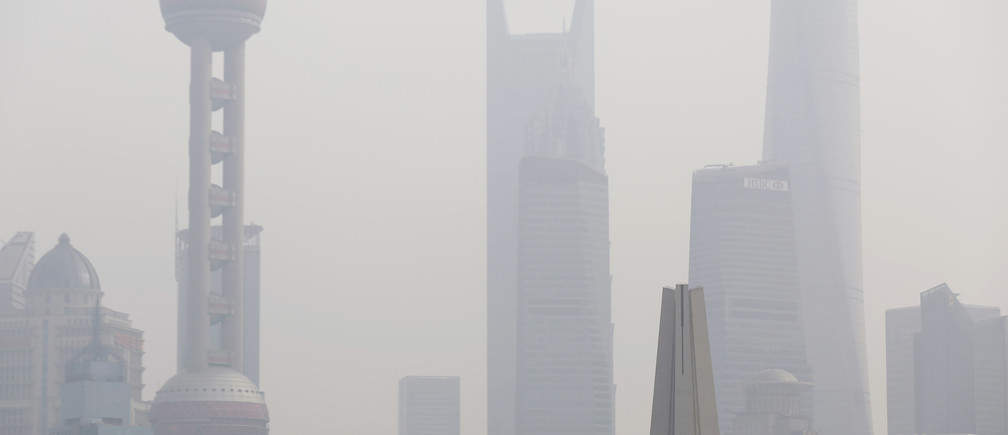 A man wearing a face mask stands on a bridge in front of the financial district of Pudong on a hazy day, in Shanghai November 17, 2014. REUTERS/Aly Song