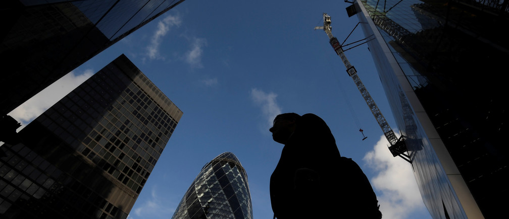 A worker walks past office skyscrapers in the City of London financial district, London, Britain, January 25, 2018. Picture taken January 25, 2018.  REUTERS/Toby Melville - RC11B1ECBCF0