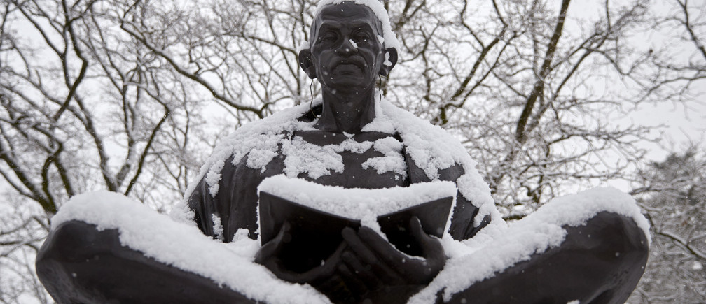 Snow falls on a statue of Mahatma Gandhi on a winter morning in the Ariana Parc outside the European headquarters of the United Nations in Geneva February 2, 2015.