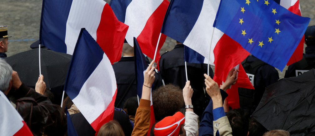 People holds French and European flags during a ceremony at the Arc de Triomphe with French President Emmanuel Macron (not pictured) after the handover ceremony in Paris, France, May 14, 2017.      REUTERS/Charles Platiau - RTX35RK1