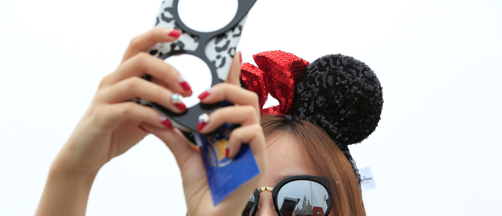 A girl takes pictures after opening ceremony at Shanghai Disney Resort in Shanghai, China, June 16, 2016. REUTERS/Aly Song - S1AETKENMJAB