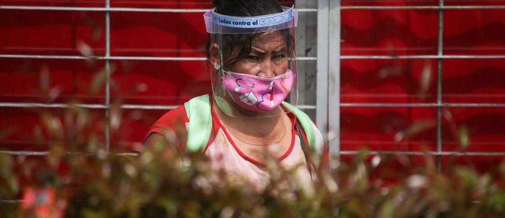 Una mujer con máscara y protector facial es vista fuera de un supermercado, después de que el gobierno permitiera a ciertos sectores volver al trabajo, en medio del brote de la enfermedad coronavirus (COVID-19) en Bogotá, Colombia, el 11 de mayo de 2020.