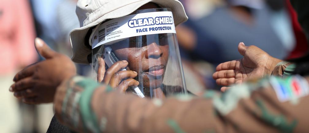Una mujer usa un protector facial durante la distribución de alimentos, mientras Sudáfrica comienza a relajar algunos aspectos de un riguroso cierre de la enfermedad coronavirus nacional (COVID-19), en Diepsloot cerca de Johannesburgo, Sudáfrica, el 8 de mayo de 2020.
