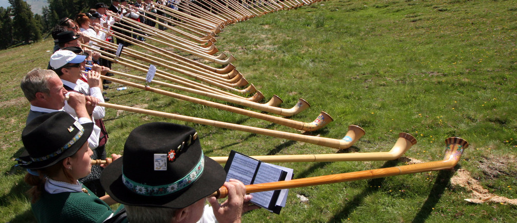 More then 100 Alphorn blowers perform during the International Alphorn contest in the southern part of Switzerland, on the alp Tracouet in Nendaz, July 23, 2006.  REUTERS/Ruben Sprich (SWITZERLAND) - RTR1FR8W