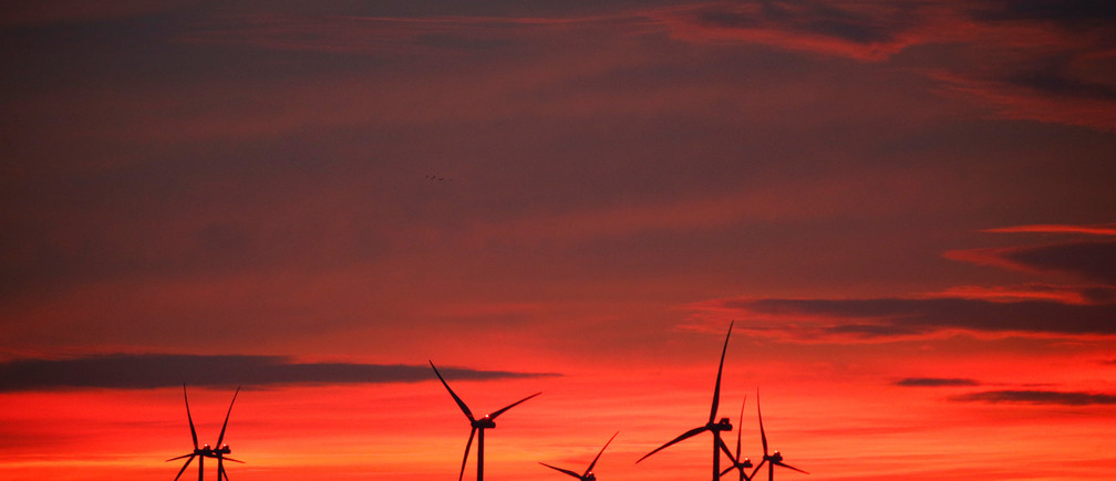 Power-generating windmill turbines are pictured at sunset at a wind park in Moeuvres near Cambrai, France, November 12, 2018