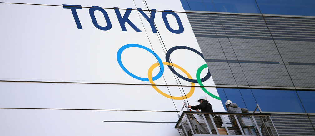 Workers put a banner on a building for the upcoming Tokyo 2020 Olympics in Tokyo, Japan March 12, 2020. REUTERS/Edgard Garrido - RC29IF99YE20