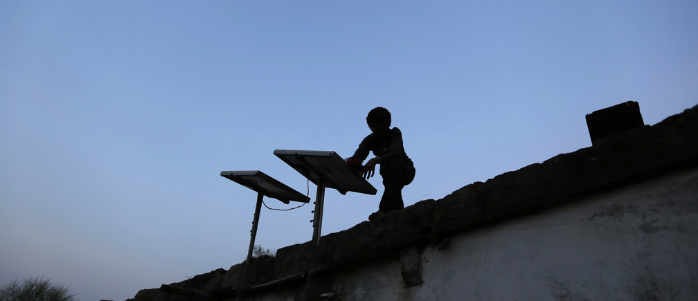 A boy dusts off a solar panel installed on the rooftop of his house on the outskirts of the western Indian city of Ahmedabad October 27, 2014.