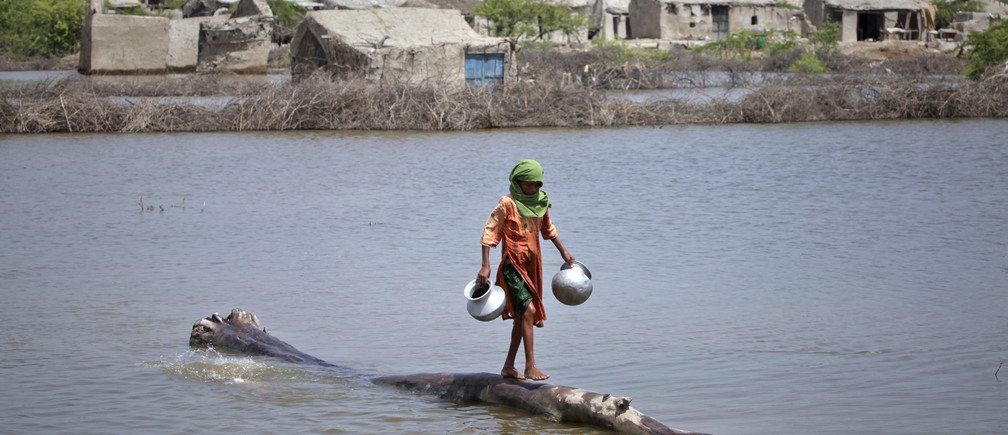 A girl, displaced by floods, carries pots as she walks on the trunk of a tree floating in the water near her home in the Badin district of Pakistan's Sindh province September 23, 2011.