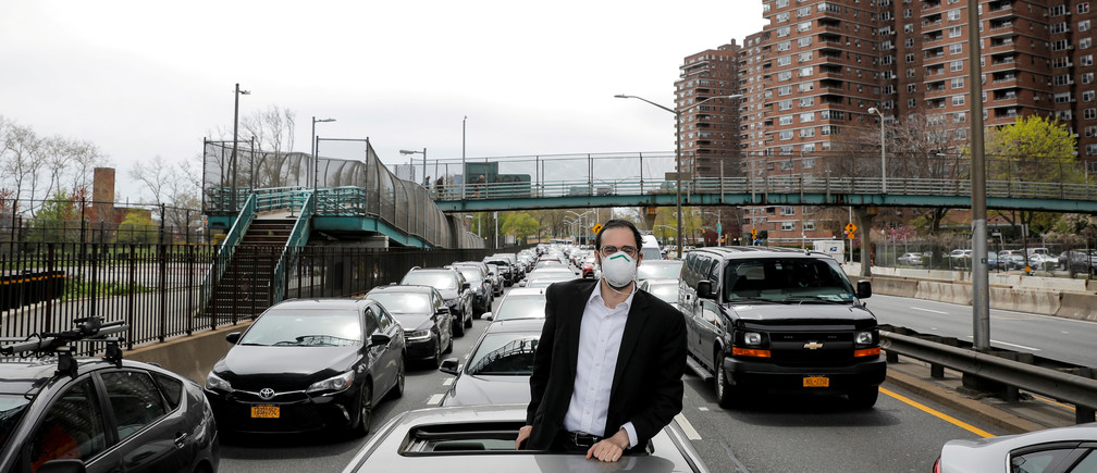 A man looks out of his car during a traffic stoppage, during the outbreak of the coronavirus disease (COVID-19) in New York City, New York, U.S., April 20, 2020. REUTERS/Andrew Kelly     TPX IMAGES OF THE DAY - RC2I8G90HRGF