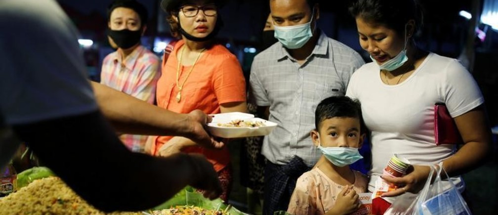 A family wearing protective masks purchases food at a market in Yangon, Myanmar, February 3, 2020. REUTERS/Ann Wang - RC24TE9ZOEO4