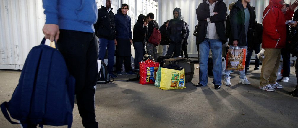 Migrants wait for a bus to leave the reception center for migrants and refugees near porte de La Chapelle in the north of Paris, France, November 25, 2016. The brand new 400-bed reception centre welcomes migrants giving them temporary refuge until French authorities find them a more permanent solution. Picture taken November 25, 2016.  REUTERS/Jacky Naegelen - RTSUP1L