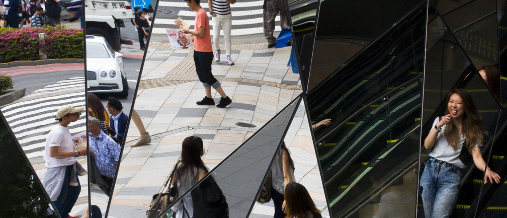 People are reflected in mirrors at an entrance to a department store in the fashion district of Harajuku in Tokyo May 15, 2015. Japan is expected to release April retail sales this week.