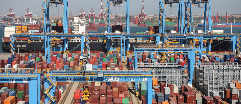 A cargo ship is seen behind containers at an automated container terminal in Qingdao port, Shandong province, China October 1, 2018. Picture taken October 1, 2018. REUTERS/Stringer ATTENTION EDITORS - THIS IMAGE WAS PROVIDED BY A THIRD PARTY. CHINA OUT. - RC12634E95E0