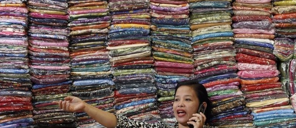 Fadhilah Arshad, a businesswoman, talks to a supplier as she sells cloth at her bazaar in Kuala Lumpur December 1, 2009. Malaysia's economy is likely to grow by 5 percent in 2010, more than official government forecasts of 2-3 percent, a top official said on Tuesday. REUTERS/Bazuki Muhammad (MALAYSIA BUSINESS) - GM1E5C117BE01
