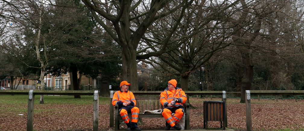 Two council workers wearing bright orange high visibility clothing smile and talk with each other as they take a break from their work at lunchtime on a dull winter's day in London, Britain January 3, 2019.   REUTERS/Russell Boyce - RC165BCC3F50