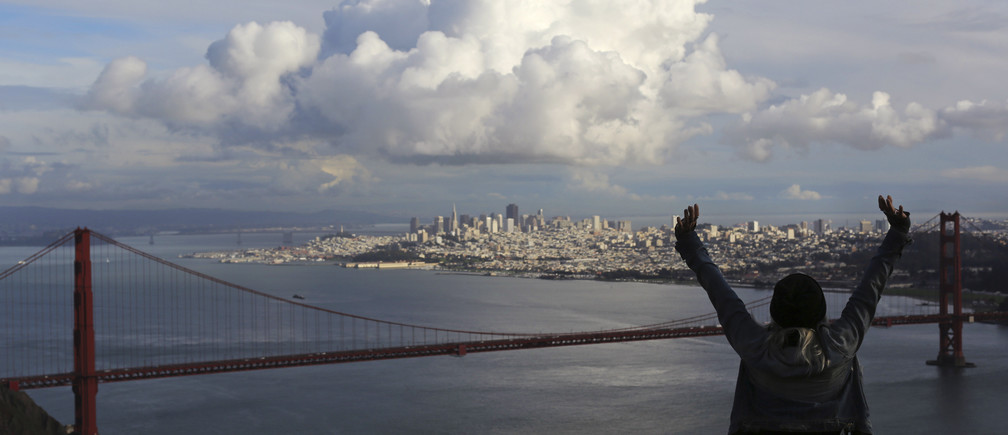 A visitor to the Marin Headlands reacts while looking out over the Golden Gate Bridge and skyline of San Francisco, as a large cloud gathers over the city, December 12, 2014. A major storm pummeled California and the Pacific Northwest with heavy rain and high winds on Thursday, killing one man, knocking out power to tens of thousands of homes, disrupting flights and prompting schools to close. REUTERS/Robert Galbraith