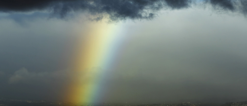 A rainbow is seen below dark clouds in San Jose city January 29, 2015.  REUTERS/Juan Carlos Ulate (COSTA RICA - Tags: SOCIETY ENVIRONMENT) - GM1EB1U0PID01