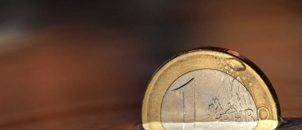 A one Euro coin is displayed in water in Munich August 20, 2012.    REUTERS/Michaela Rehle (GERMANY  - Tags: BUSINESS POLITICS)   - LR1E88L14D117