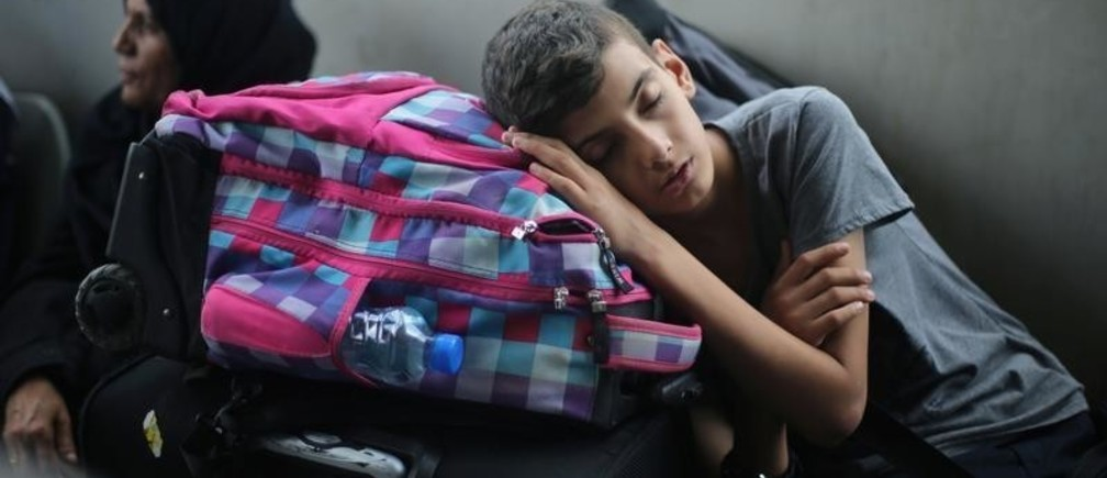 A Palestinian boy sleeps as he waits with his family for a travel permit to cross into Egypt through the Rafah border crossing after it was opened by Egyptian authorities for humanitarian cases, in Rafah in the southern Gaza Strip August 16, 2017. REUTERS/Ibraheem Abu Mustafa - RC121081F420
