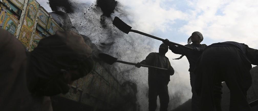 Labourers shovel coal onto a truck at a coal dump site outside Kabul January 23, 2014. REUTERS/Omar Sobhani