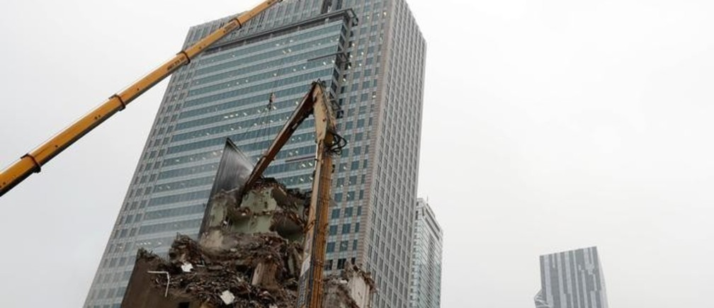 An excavator demolishes a building near skyscrapers in the centre of Warsaw, Poland November 9, 2017. Picture taken November 9, 2017. REUTERS/Kacper Pempel