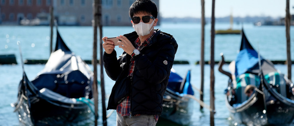 A tourist wears a protective mask in Saint Mark's Square as the Italian government prepares to adopt new measures to contain the spread of coronavirus in Venice, Italy, March 8, 2020. REUTERS/Manuel Silvestri - RC2OFF9ST6KT