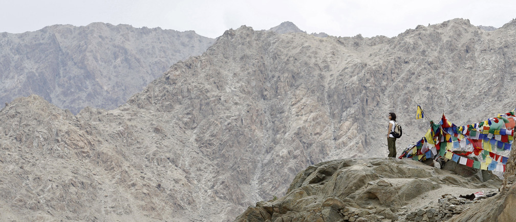 An Italian tourist stands on a hilltop overlooking Leh city, capital of Ladakh July 8, 2011