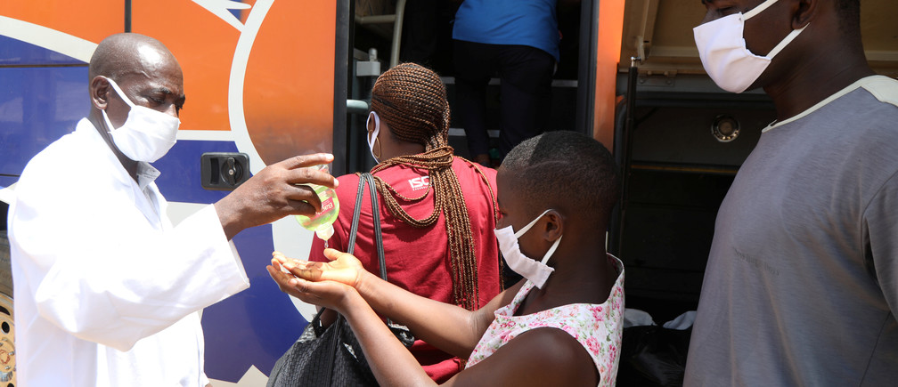 A health worker puts hydroalcoholic gel on the hands of a pupil as she boards a government chartered bus convoy, which will take students and teachers back to cities and schools of the countryside, as the lockdown due to coronavirus disease (COVID-19) is eased, in Abidjan, Ivory Coast May 19, 2020. Picture taken May 19, 2020. REUTERS/Luc Gnago - RC2PVG9294A5