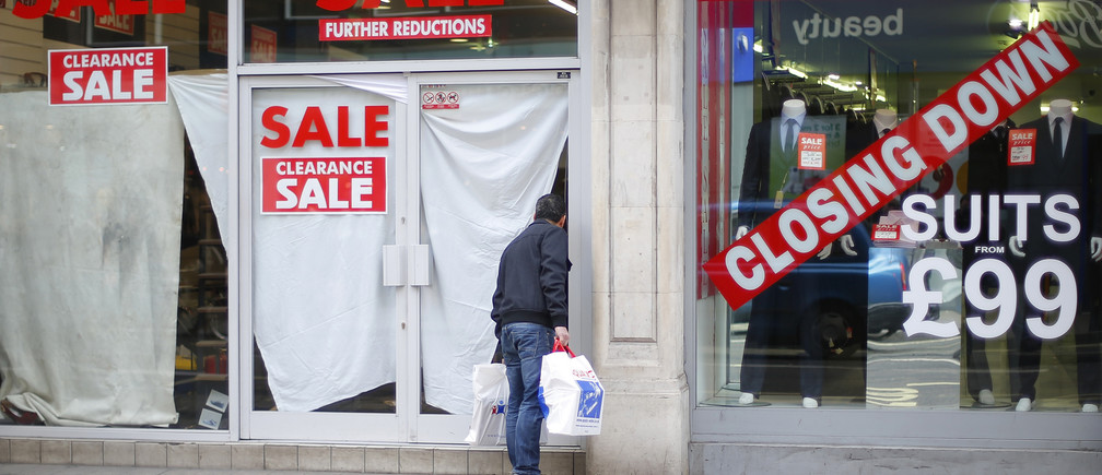 A man peers into a closed down shop, next door to another shop holding a closing down sale, in central London February 27, 2013. Britain's economy contracted by 0.3 percent in the last quarter of 2012 as first thought, keeping alive the danger of a third recession since 2008, although yearly growth was revised up, data showed on Wednesday. REUTERS/Andrew Winning (BRITAIN - Tags: POLITICS BUSINESS) - LM1E92R1CFH01