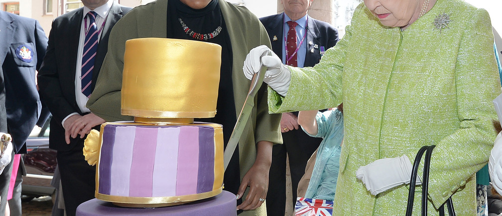 Britain's Queen Elizabeth cuts the cake Nadiya Hussain, winner of the Great British Bake Off baked for her, as she walks through Windsor on her 90th Birthday, in Windsor, Britain April 21, 2016. REUTERS/John Stillwell/Pool - LR1EC4L11IFFY