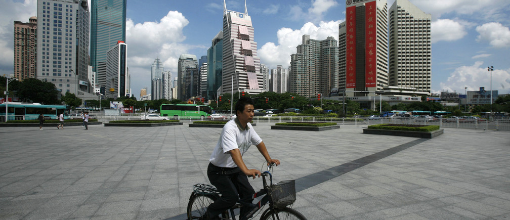 A man cycles past downtown Shenzhen in southern, Guangdong province September 5, 2010, one day before a ceremony to mark the 30th anniversary of the establishment of this special economic zone.