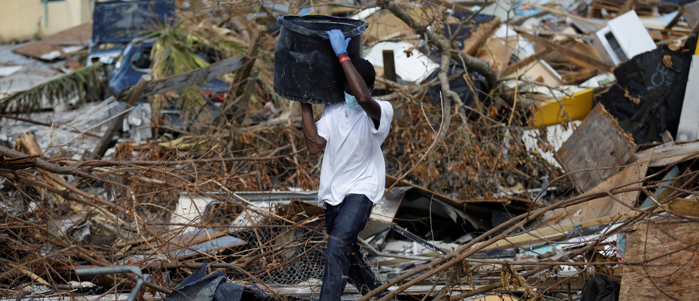 A man carries a container during a search for the dead operation in the destroyed the Mudd neighbourhood after Hurricane Dorian hit the Abaco Islands in Marsh Harbour, Bahamas, September 10, 2019. REUTERS/Marco Bello - RC1C8427DCB0