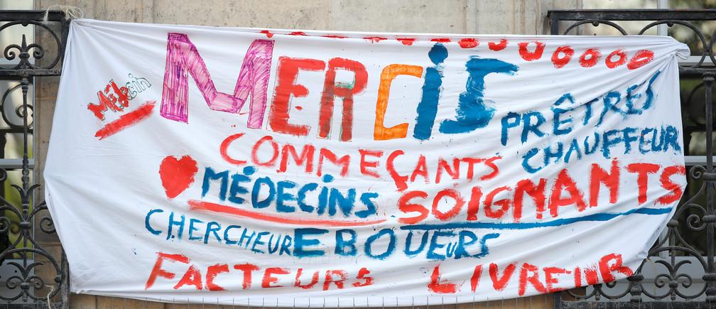 """Une banderole sur laquelle on peut lire """"Merci aux prêtres, aux chauffeurs, aux médecins, aux commerçants, au personnel médical, aux chercheurs, aux éboueurs, aux facteurs"""" est placée sur un balcon pour soutenir les soignants et les travailleurs pendant la Journée mondiale de la santé, alors que la propagation de la maladie à coronavirus (COVID-19) se poursuit, à Paris, France, le 7 avril 2020."""
