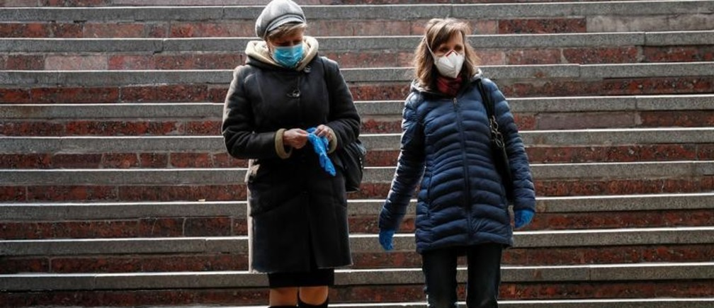Women wearing protective masks, as a preventive measure against coronavirus disease (COVID-19), walk downstairs in an underpass in central Kiev, Ukraine March 30, 2020. REUTERS/Gleb Garanich - RC2EUF9BKFKS